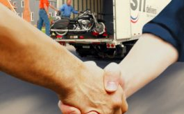 Men Shaking Hands in Front of Motorcycle Transport Truck